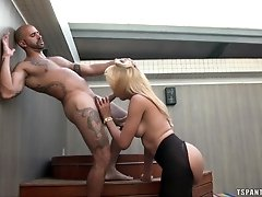 Blonde shemale is on her knees, giving a blowjob to a bald guy. She's...